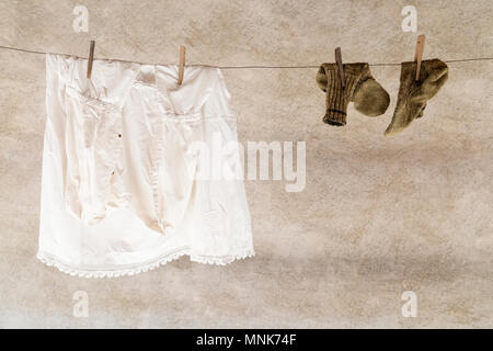 A white shirt and a pair of knitted woolen socks hanging on a laundry rope with wooden clothespins - Stock Photo