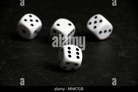 Four white and black dice on a black table - Stock Photo