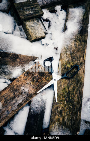 Conceptual discarded scissors on frozen woodpile in winter snow - Stock Photo
