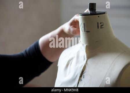 Pattern Maker (Fashion): a real Pattern Maker/Pattern Cutter at work on a calico toile on a model stand, or mannequin - Stock Photo
