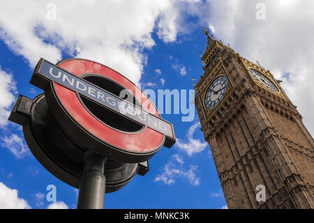 LONDON, UK - AUGUST, 11 2013; The sign of the London Underground and the Big Ben at the Westminster Tube station in London. - Stock Photo