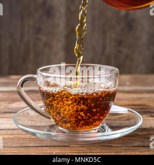 Photography pours tea in cup - Stock Photo