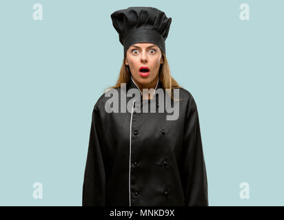 Young cook woman scared in shock, expressing panic and fear - Stock Photo