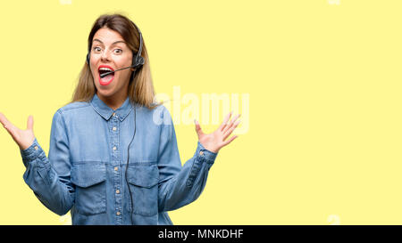 Consultant of call center woman in headphones happy and surprised cheering expressing wow gesture - Stock Photo