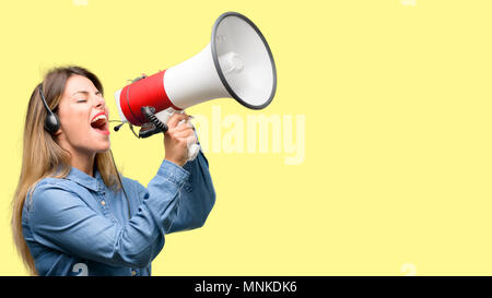 Consultant of call center woman in headphones communicates shouting loud holding a megaphone, expressing success and positive concept, idea for market - Stock Photo