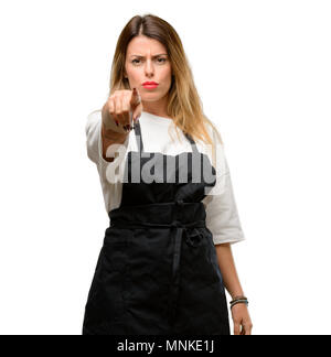 Shop owner woman wearing apron pointing to the front with finger - Stock Photo