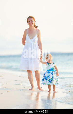 Vertical photo of young mother and her adorable little daughter standing on the beach at sunset time - Stock Photo