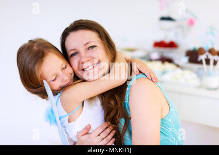 Mother and her adorable little daughter on a birthday party - Stock Photo