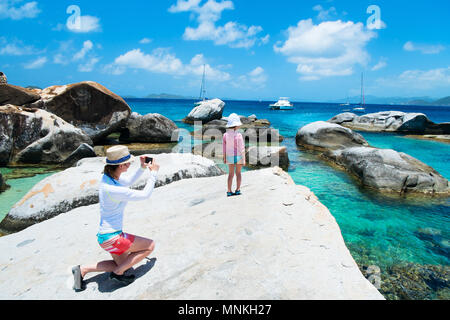 Mother photographing her little daughter at The Baths beach area major tourist attraction at Virgin Gorda, British Virgin Islands, Caribbean - Stock Photo