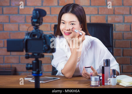 Young happy asian woman online cosmetic seller vlogging to her fan page showing how to put make up on - Stock Photo