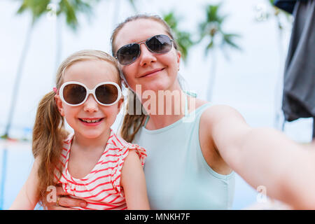 Happy family mother and her adorable little daughter on summer vacation taking selfie with smartphone - Stock Photo