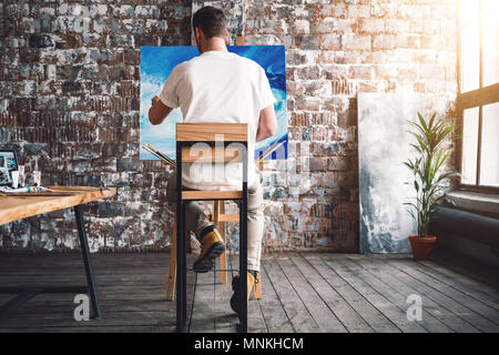 Male painter sits on chair in front canvas and drawing picture in studio. Art class and workshop. Artist painting process. Hobby - Stock Photo