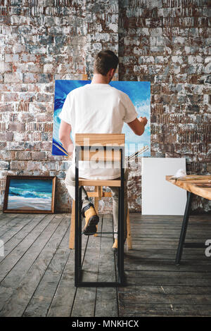 Male painter sits on chair in front canvas and drawing picture in studio. Art class and workshop. Artist painting process. Hobby. Vertical - Stock Photo