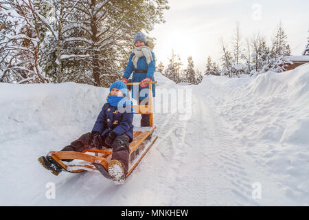 Beautiful family of mother and daughter enjoying snowy winter day outdoors having fun sledging - Stock Photo