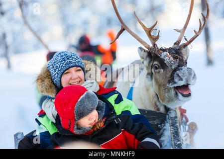 Family of mother and little girl at reindeer safari in winter forest in Lapland Finland - Stock Photo