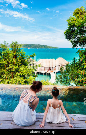 Happy mother and her adorable little daughter outdoors near infinity swimming pool at tropical resort enjoying views over overwater bungalows - Stock Photo