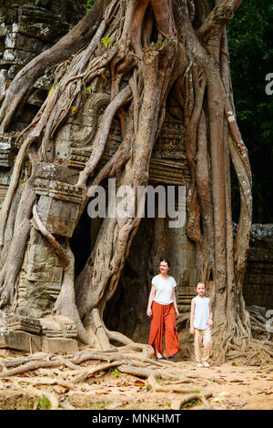 Family visiting ancient Ta Som temple in Angkor Archeological area in Cambodia - Stock Photo