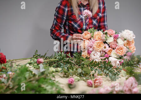 Female florist. Floral workshop - woman making a beautiful flower composition a bouquet. Floristry concept - Stock Photo
