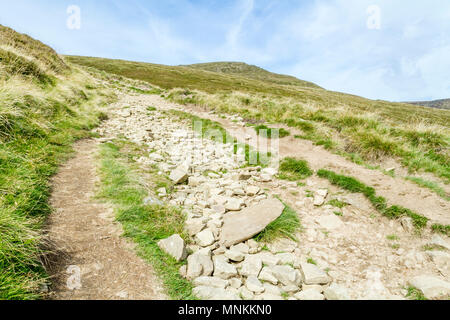 An uphill dry rough stony footpath to Grindslow Knoll on Kinder Scout during Summer. Derbyshire, Peak District, England, UK - Stock Photo