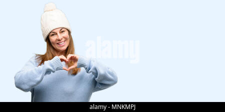 Middle age woman wearing wool winter cap happy showing love with hands in heart shape expressing healthy and marriage symbol isolated blue background - Stock Photo