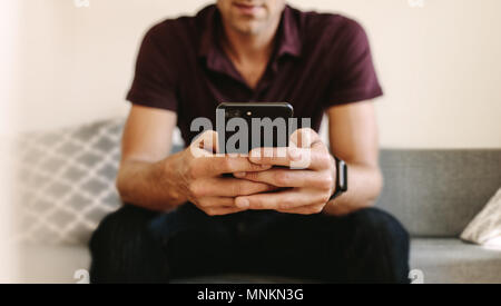 Close up of man working on mobile phone sitting on sofa. Man operating mobile phone with two hands. - Stock Photo