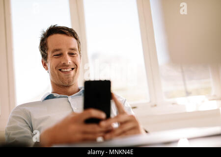 Smiling entrepreneur working on mobile phone sitting in the comfort of home. Man operating mobile phone while relaxing at home. - Stock Photo