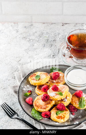 Healthy summer breakfast, cheese pancakes with raspberry, powdered sugar and mint, grey concrete background copy space - Stock Photo