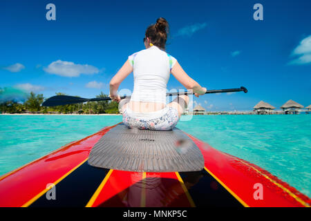 Back view of young sporty woman on paddle board - Stock Photo