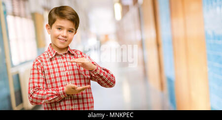 Handsome toddler child with green eyes holding something, size concept at school corridor - Stock Photo