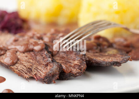german sauerbraten with red cabbage on a plate - Stock Photo