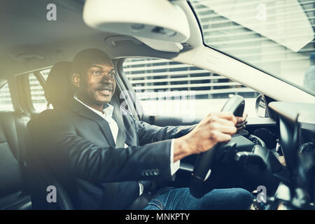 Smiling African businessman wearing a blazer driving his car during his morning commute to work - Stock Photo