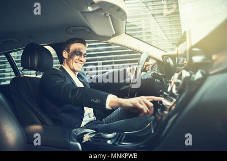 Smiling young businessman wearing a blazer changing radio stations while driving his car through the city during his morning commute to work - Stock Photo