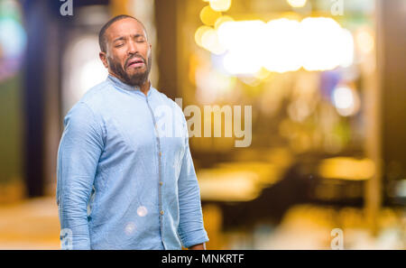 African american man with beard crying depressed full of sadness expressing sad emotion at night - Stock Photo
