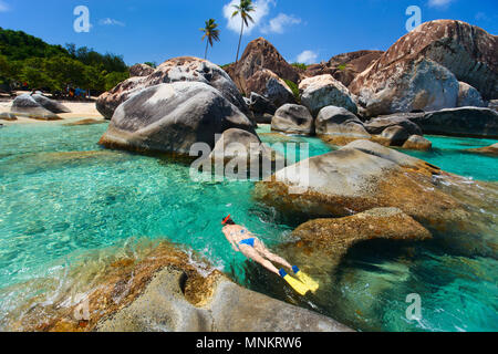 Young woman snorkeling in turquoise tropical water among huge granite boulders at The Baths beach area, British Virgin Islands, Caribbean - Stock Photo