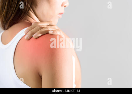 woman holding hand on skin around right shoulder joint with inflammation color - Stock Photo