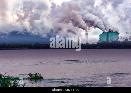 factory pollution nearly river and mountain - Stock Photo