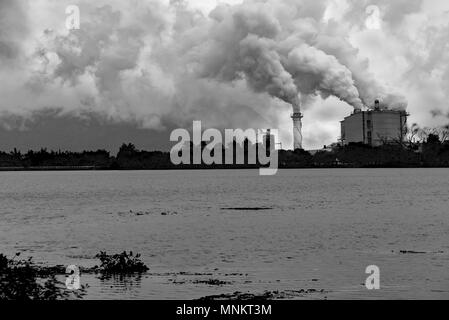 black and white factory pollution nearly river and mountain - Stock Photo