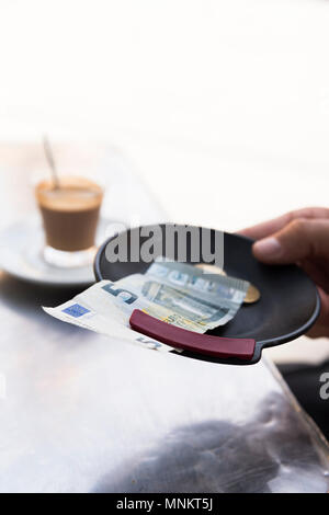 closeup of a young man sitting at a table in the terrace of a cafe paying the bill with a five euros banknote and some coins - Stock Photo