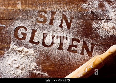 high-angle shot of a wooden table sprinkled with a gluten free flour where you can read the text sin gluten, gluten free written in spanish, next to a - Stock Photo