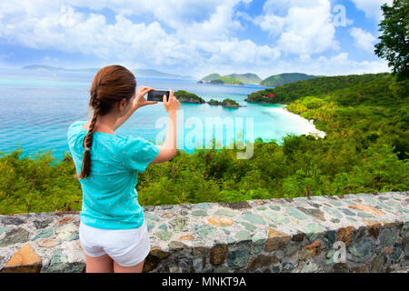 Back view of tourist girl taking photo with mobile cell phone of Trunk bay on St John island - Stock Photo
