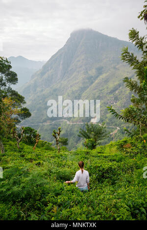 Young woman enjoying breathtaking views over mountains and tea plantations in Ella Sri Lanka - Stock Photo