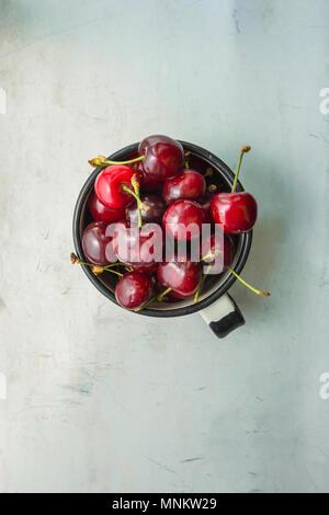 Ripe Organic Freshly Picked Sweet Cherries in Vintage Enamel Mug on Grey Metal Stone Concrete Background by Window. Garden Table. Flat Lay. Summer Har - Stock Photo