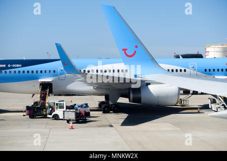 TUI Boeing aircraft on the apron of a busy airport . GSE are servicing a plane. The planes clearly display the TUI logo and on the planes tail - Stock Photo