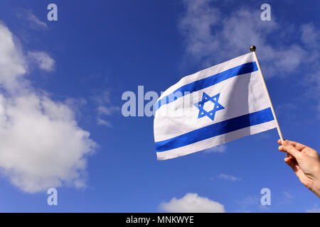 Woman wave flag of Israel against blue sky and white clouds on Israels 70's independent day. - Stock Photo