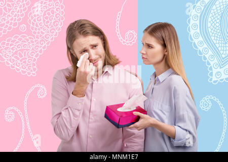 Kind wife comforting her crying husband and looking at him - Stock Photo