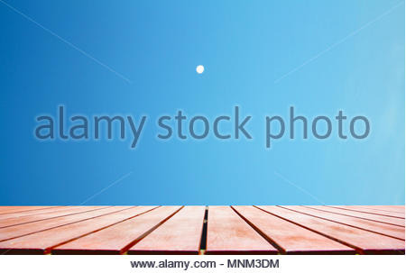 Wooden floor and Light gradient clear blue morning sky with small white almost full round moon background - Stock Photo