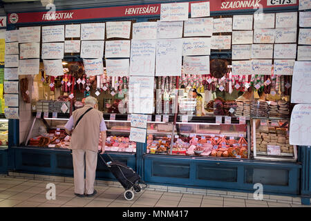An unidentified man with a cart shops for meat at the Central Market in the Pest section of Budapest, Hungary. - Stock Photo