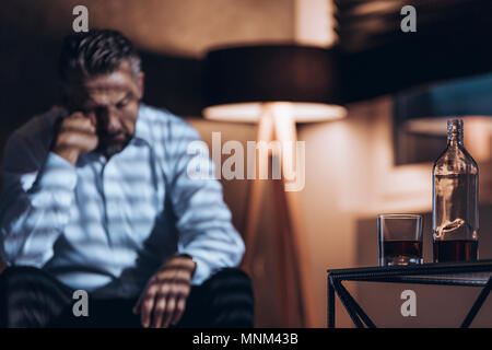 Bottle and glass with alcohol in the foreground and wasted addict sitting in the back (blurred) - Stock Photo
