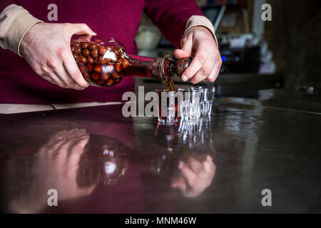 Ginjinha being poured at a traditional bar in Lisbon, Portugal. - Stock Photo