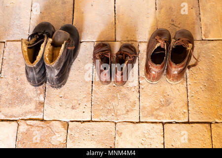 Top view of three pairs of old worn leather shoes in a line on beige stone floor. - Stock Photo